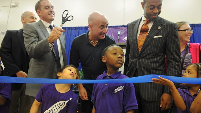 Andre Agassi and State Rep. Harold Love Jr. joke with students before the grand opening of Rocketship Education's Nashville Northeast Elementary charter school on Dickerson Pike on Sept. 16, 2014. Agassi is a partner in a group that bankrolls the construction of charter school buildings.