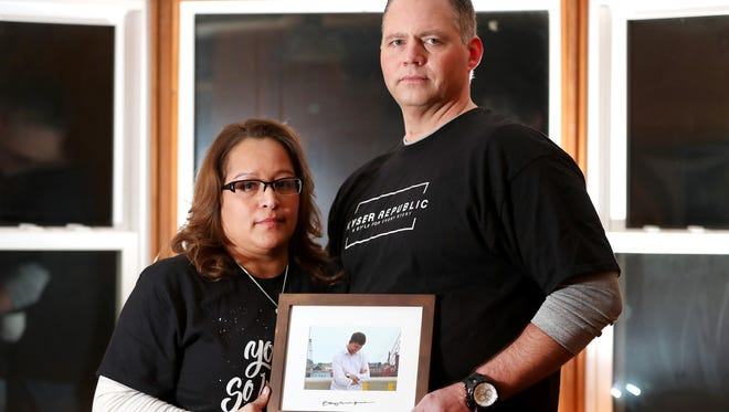 Donna Kyser and Rod Boldt hold a photo of Ben Kyser at their home in Winneconne. Ben Kyser died by suicide in August.