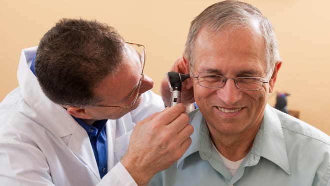 Audiologist doing an ear canal inspection