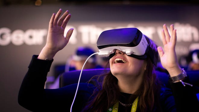 A woman reacts as she uses a new Samsung Gear 360, a 360-degree camera, at the Mobile World Congres