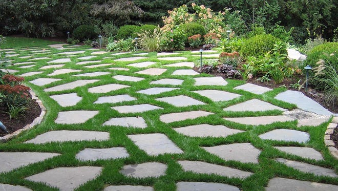 Five-inch-thick bluestone with sod joints can double as a driveway and a patio. Good drainage is the key to keeping the grass intact over the winter. The grass gets cut with a lawn mower.