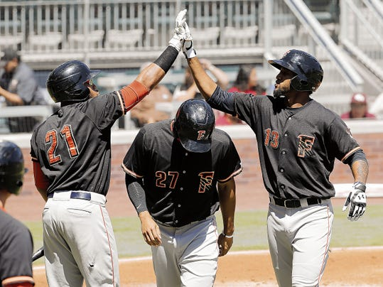 MARK LAMBIE—EL PASO TIMES Fresno's Domingo Santana, right, celebrates his homer against El Paso Tuesday. Fresno sent six hits over the wall on their way to beating El Paso 12-2.