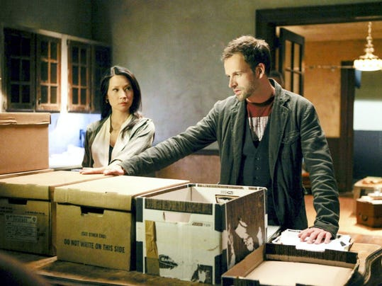 "Dr. Joan Watson (Lucy Lui) and Sherlock Holmes (Jonny Lee Miller) confront the a preponderance of seized documents they must wade through in an episode of ""Elementary."""