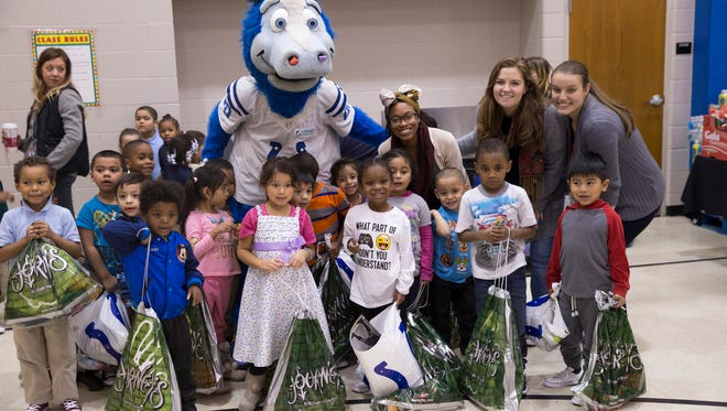 Blue, the Colts mascot, poses with kids during the Cold Feet, Warm Shoes & Hats event sponsored by Lids and the colts, as a benefit for kids including these at IPS School 63, Indianapolis, Tuesday, Dec. 5, 2017.