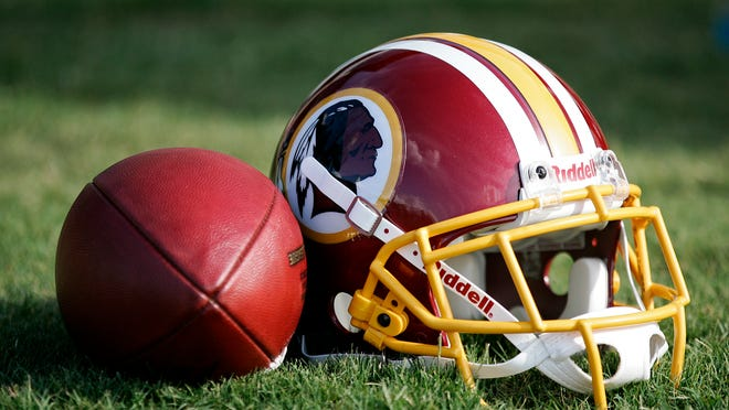 Jul 26, 2013; Richmond, VA, USA;  A Washington Redskins player's helmet and NFL football rest on the field after practice during 2013 NFL training camp at the Bon Secours Washington Redskins Training Center. Mandatory Credit: Geoff Burke-USA TODAY Sports ORG XMIT: USATSI-139166 [Via MerlinFTP Drop] uspf