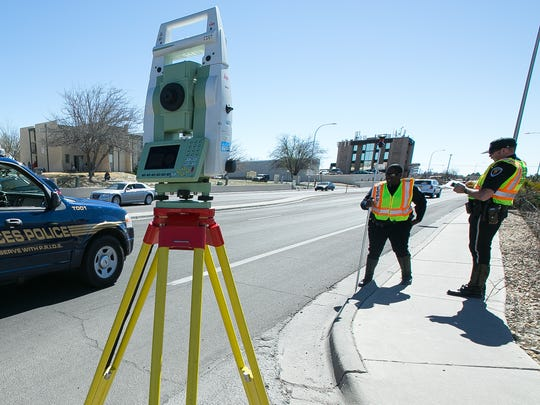 Las Cruces police officers Daniel Thomas, left, and Thaddeus Allen take measurements Tuesday on Telshor Boulevard near Celebrate liquor store where Romy M. Chavarria, 63, was killed after being struck by a vehicle Monday evening.