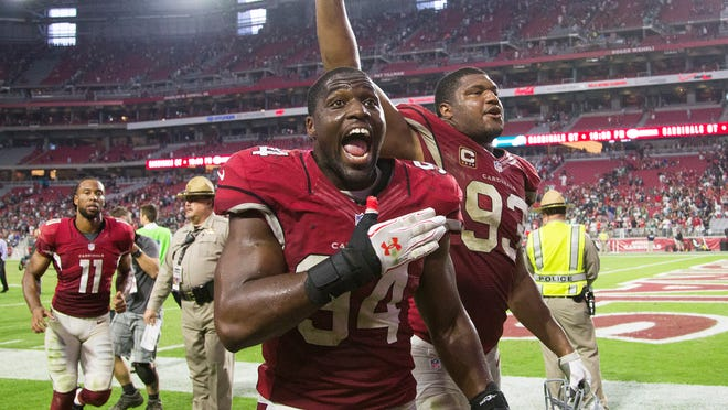 Cardinals linebacker Sam Acho (94) and defensive lineman Calais Campbell leave the field with glee as receiver Larry Fitzgerald follows after Arizona's 24-20 win over Philadelphia on Sunday.