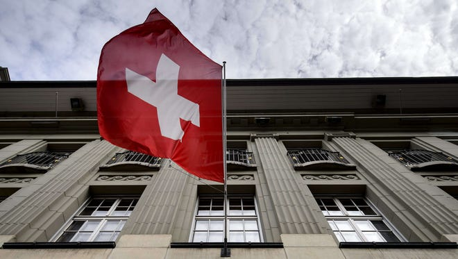 A Swiss flag flies over a building in Switzerland.