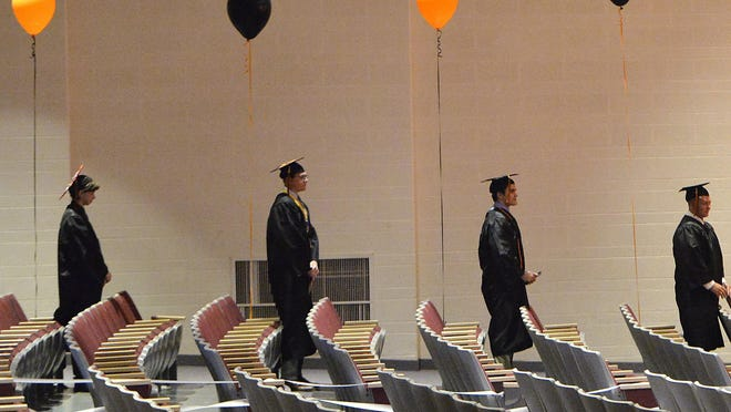 Harbor Creek High School seniors stand during a commencement ceremony on May 29, 2020, in Harborcreek Township. Friday was the first of three days recognizing graduating seniors. Groups of seven seniors and their families were allowed in the school's auditorium where each student walked across the stage to receive their diploma. Seats in the auditorium were cleaned after each use, due to the COVID-19 coronavirus pandemic.