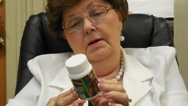 Deanna Bertrand of Morris, Ga., reads the label on a bottle of Reumofan she purchased online. Bertrand has been taking Reumofan for about a year to ease her knee pain.