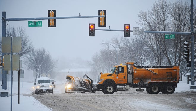 A City of Sioux Falls Public Works plow clears 49th Street during the first snow of the season Friday, Nov. 20, 2015, in Sioux Falls.