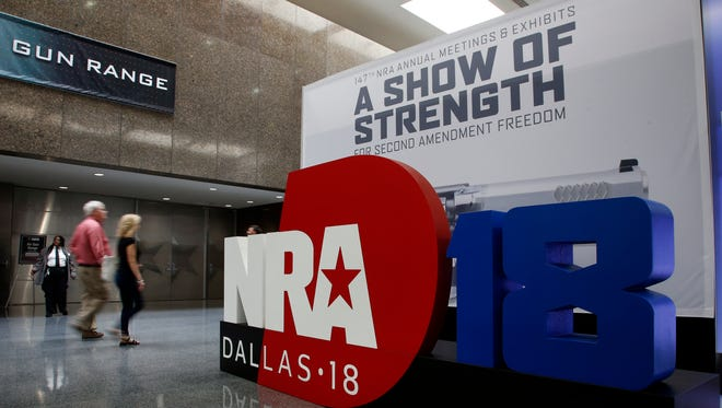 People walk by NRA convention signage in the Kay Bailey Hutchison Convention Center in Dallas, May 3, 2018. The convention is scheduled to go through Sunday.