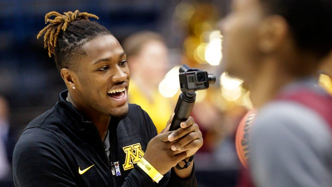 Injured Minnesota guard Akeem Springs takes a video of his team during practice.