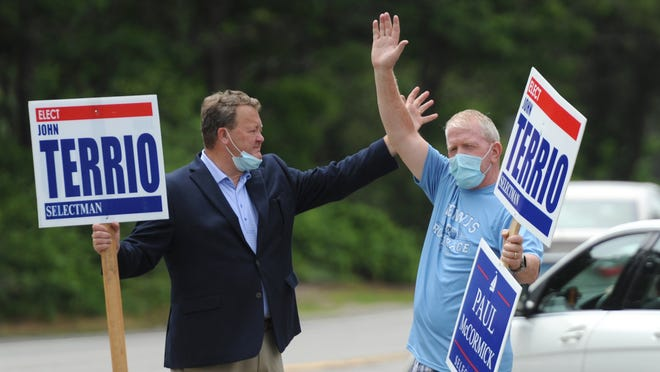 Dennis resident Brian Carey, right, joined Selectman John Terrio outside Dennis Town Hall and the adjacent police station to greet voters during Tuesday's annual town election. Carey was elected as a write-in candidate to the Denis-Yarmouth Regional School Committee, while Terrio won reelection to the Board of Selectmen.
