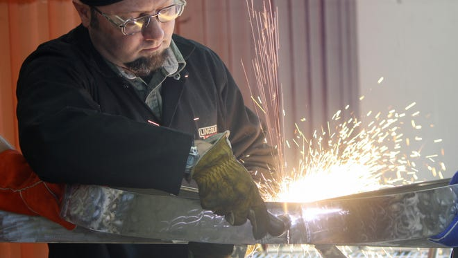 Tom Sumerix, welding program chair, uses a plasma cutter to cut a carbon steel ribbon at Cincinnati State Technical and Community College. The school will open a new 12-booth welding lab at its Clifton campus.