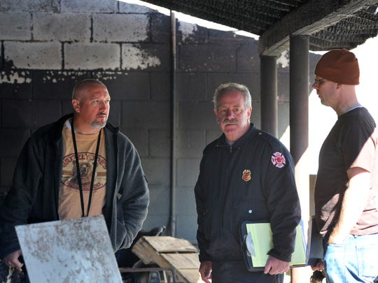 Downtown Grocery owner Kevin Korpela, right, looks Wednesday at damage from the fire.