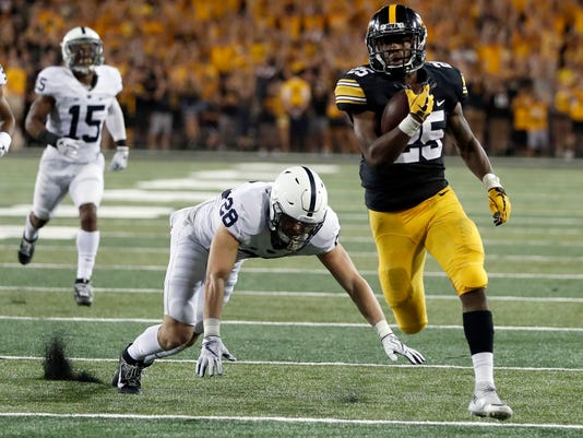 FILE - In this Sept. 23, 2017, file photo, Iowa running back Akrum Wadley, right, scores past Penn State cornerback Grant Haley (15) and safety Troy Apke during the second half of an NCAA college football game in Iowa City, Iowa. Wadley needs 138 yards to reach 1,000 rushing yards. He would become the fourth Hawkeye, and first since Fred Russell in 2002-03, to have back-to-back 1,000-yard seasons. (AP Photo/Jeff Roberson, File)