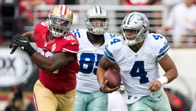Dallas Cowboys quarterback Dak Prescott (4) runs with the football against San Francisco 49ers defensive lineman DeForest Buckner (99) during the first quarter at Levi's Stadium.