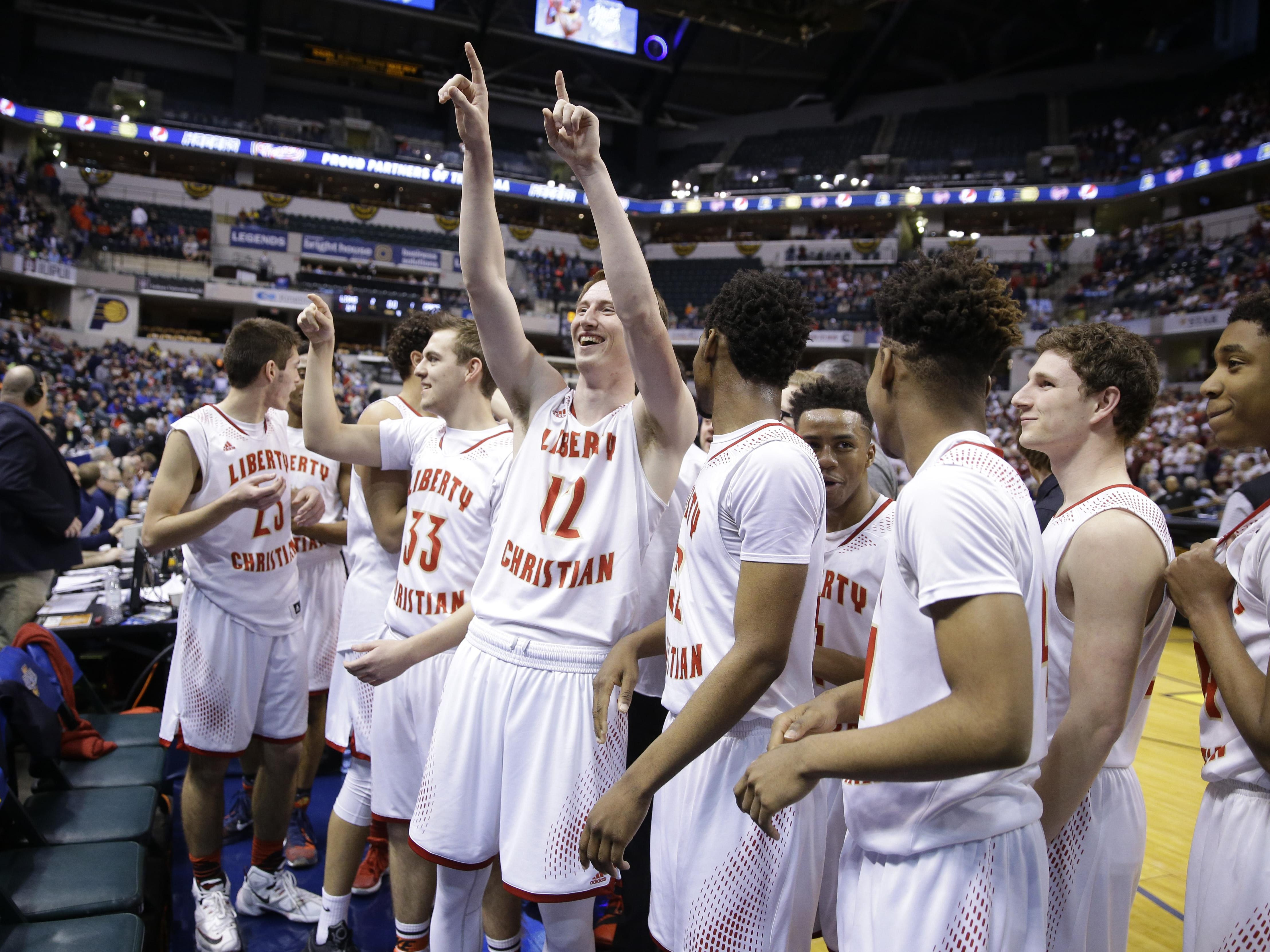 Liberty Christian players, including Caleb Hardy (12) celebrate after winning the Class A state championship basketball game over Bloomfield at Bankers Life Fieldhouse, Saturday.