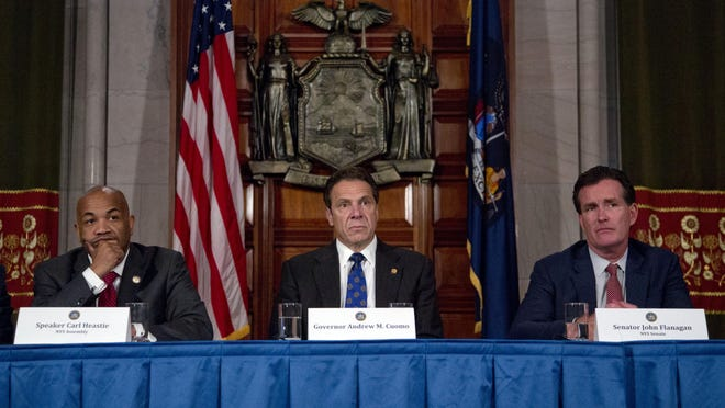 Assembly Speaker Carl Heastie, D-Bronx, left, New York Gov. Andrew Cuomo and Senate Majority Leader John Flanagan, R-Smithtown, during a news conference on Thursday, June 25, 2015, in Albany, N.Y. (AP Photo/Mike Groll)