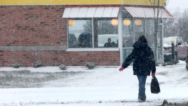 A person walks along South Church near South Rutherford in the snow on Tuesday, Jan. 16, 2018.