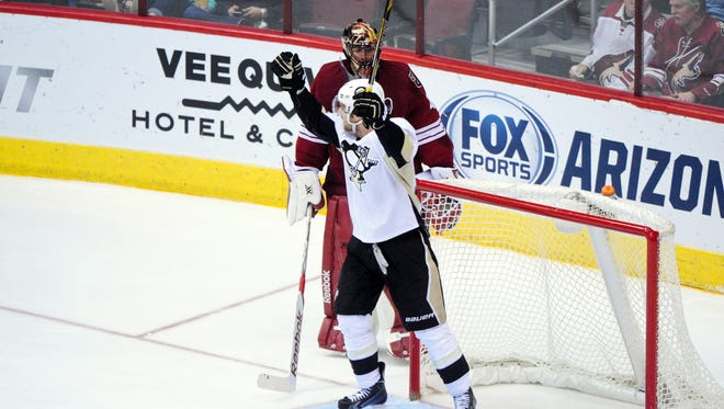 Mar 21, 2015: Pittsburgh Penguins center Brandon Sutter (16) celebrates a power play goal as Arizona Coyotes goalie Mike Smith (41) looks on on the second period at Gila River Arena.