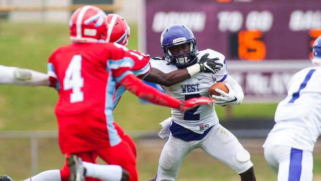 Harrison Hand of Cherry Hill West fights off a Pennsauken defender en route to a short gain in Saturday's game.