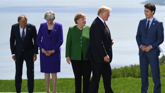 European Council President Donald Tusk, left, Britain's Prime Minister Theresa May, German Chancellor, Angela Merkel, President Donald J. Trump and Canadian Prime Minister, Justin Trudeau prepare for the Family Portrait at the G7 summit, Friday.