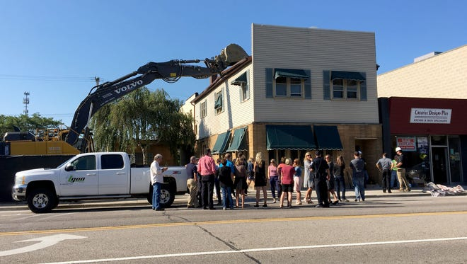 A crowd of Brighton city employees, council members, business owners and others gather outside 317 W. Main Street Tuesday, Aug. 8, 2017, where demolition of the existing building was set to begin after a groundbreaking ceremony for two new buildings containing restaurants, upscale apartments and office space.