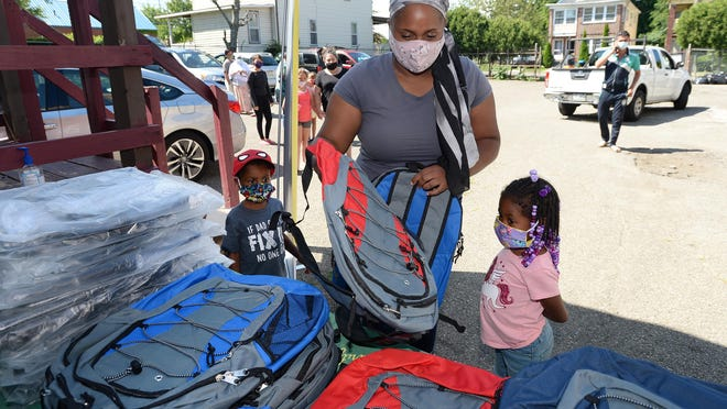 Jasmine Newby, 22, of Erie, and her children, Shyheed, 4, left, and Trinity 6, right, get new backpacks Saturday at the Islamic Association of Erie. The association was passing out free back-to-school supplies for Erie residents.