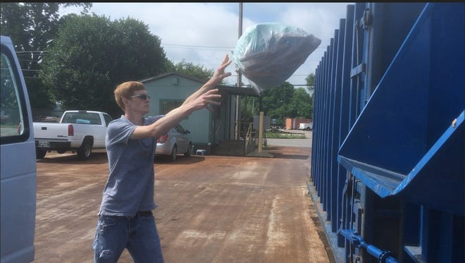 Tyler Heerdink  throws trash into compactor for garbage bin Thursday June 14, 2018, at Murfreesboro's West Main Street Convenience Center. The City Council agreed to reduce days of operation at the center that also collects recycling materials from six to three on Tuesdays, Wednesdays and Fridays to save money.