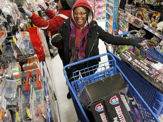 Anjah Harper, Rochester, center, happily fills her cart with more items as she shops with friend Renata Faines of Buffalo, left,  at Toys R Us in Greece on Thursday.