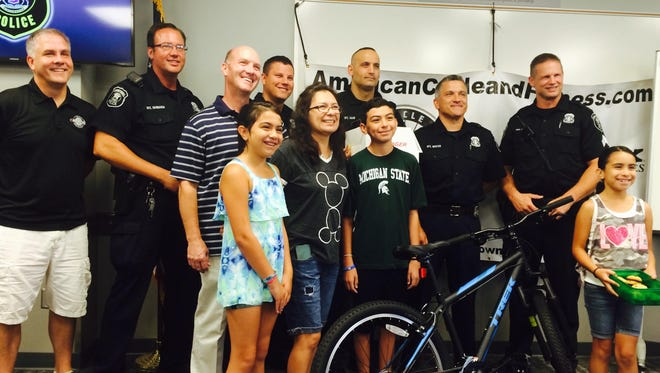 (From left) Ken Stonehouse, owner of American Cycle and Fitness, police officers and family members surround Erik Saperstein after he's presented a new bike from the Farmington Hills Police Department.