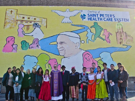 "Parishioners of the Holy Family Parish at Sacred Heart Church on Throop Avenue join Monsignor Joseph Kerrigan, center, during the dedication on Sunday, Nov. 30, of a mural that was painted on an exterior wall of the Holy Family Parish headquarters. Tabiri Chukunta, executive director of community outreach for Saint Peter's Healthcare System, stands at the left shoulder of Kerrigan.  The mural shows Pope Francis in profile surrounded by images emblematic of the Catholic Church. The mural is the work of local artist Pavol Olsavsky III, who worships at the church. The mural was sponsored by Saint Peter's Healthcare System.  Kerrigan noted, ""By literally transforming one brick wall into a colorful work of art, we express our shared commitment and vision of healthy, vibrant family life in New Brunswick. The mural is our expression of the team effort needed to put Pope Francis' vision in action in our city."""