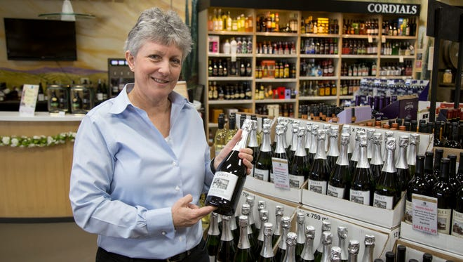 Julie Crowley, owner of Triphammer Wines and Spirits, displays a bottle of Glenora Wine Cellars wine with a special label commemorating the store's 75th anniversary.