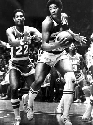 In this Jan . 30, 1979, file photo, Wes Unseld of the Washington Bullets takes in an offensive rebound against John Drew (22) of the Atlanta Hawks during the first half of an NBA game in Landover, Maryland. Unseld, the workmanlike Hall of Fame center who led Washington to its only NBA championship and was chosen one of the 50 greatest players in league history, died Tuesday after a series of health issues, most recently pneumonia. He was 74.