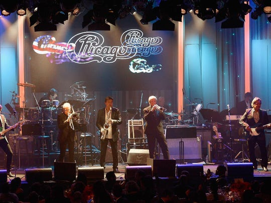 Keith Howland (far left), Walfredo Reyes Jr. (seated on drum riser), James Pankow, Walter Parazaider, Lee Loughnane, Tris Imboden (seated on drum riser), Robert Lamm (back right) and Jason Scheff of Chicago perform during a pre-Grammy event Feb. 14. The band will play in Milwaukee on Thursday night at the BMO Harris Bradley Center with Earth, Wind & Fire.