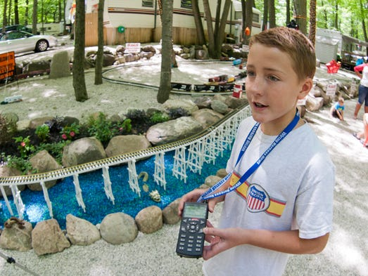 Andrew Gray holds the controller Saturday July 5, 2014 he uses for his the model railroad that his family built for him at their Plymouth Rock campground site. Gray, who has Aspergers is keenly interested in the workings of trains.