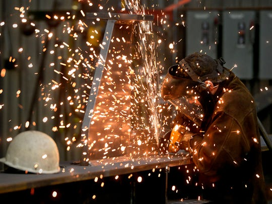 A welder at ADF sands a weld on a steel support beam in 2015.