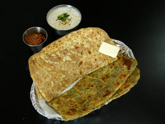 Flatbreads at Indian Delight include methi paratha, filled with fenugreek leaves, and paneer paratha, filled with fresh cheese.