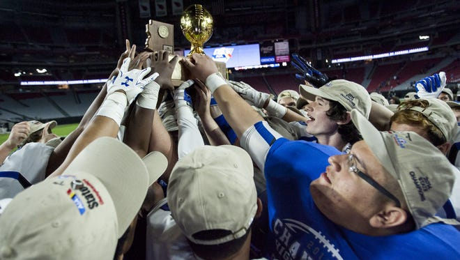 The Chandler Wolves reach for the Div. I state championship trophy after winning against the Hamilton Huskies, 28-7, Nov. 28, 2014 in Glendale.