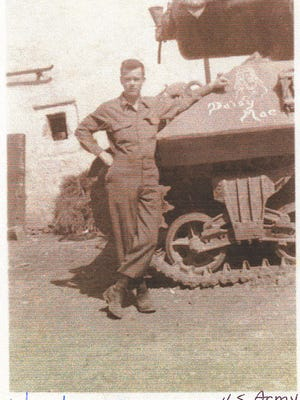 Elmer Staib standing by one of the tanks in the 610 Tank Battalion during WWII, European Theatre.