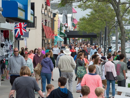 Visitors to Rehoboth Beach walk next to shops along Rehoboth Avenue.