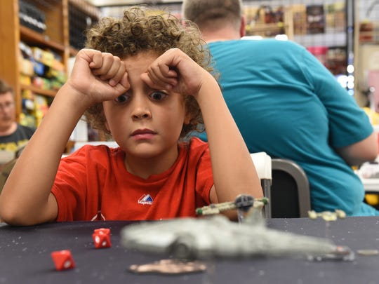 Randy Carr, 8, eyes his roll while he and his father Adam, play a round of Star Wars X-Wings Miniature Game during a board game night at Comic Store West in Springettsbury Township.