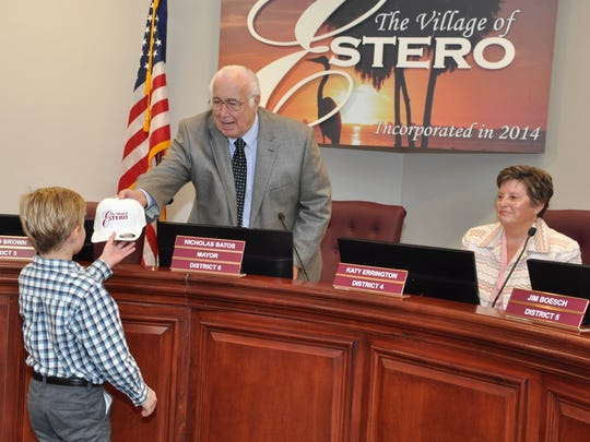 Estero Mayor Nick Batos presents nine-year-old Nicky Snow with a Village of Estero ball cap after Snow led the council in the Pledge of Allegiance Wednesday.