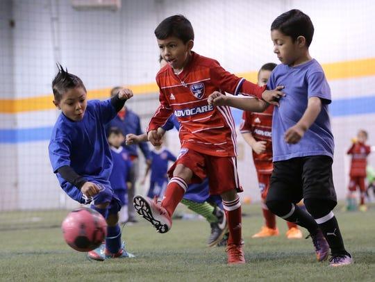 An FC Dallas player shoots between a pair of La U players