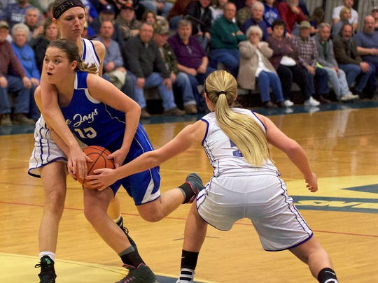 Johnstown Christian's Beth Felix, center, tries to drive the lane against McConnnellsburg's Bronwyne Mellott, right, and Alexis Mellott on Friday night. Felix scored 25 points, but it wasn't enough to overcome the Spartans in a 69-48 loss.