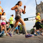 Participants of the 2015 17th Flying Pig Marathon and Half Marathon take off past the starting line along Mehring Way on Sunday, May 3.