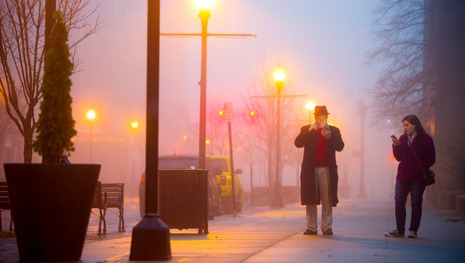 Rick and Danielle Cory, both of Evansville, walk along Main Street through dense fog playing Pokemon Go, Sunday, Dec. 25, 2016. The National Weather Service has issued a Dense Fog Advisory for the region until 10 p.m.