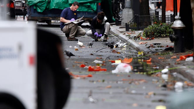 Evidence teams investigate at the scene of Saturday's explosion on West 23rd Street in Manhattan's Chelsea neighborhood, Monday in New York. Ahmad Khan Rahami, wanted in the bombings that rocked Chelsea and a New Jersey shore town, was captured Monday after being wounded in a gun battle with police that erupted when he was discovered sleeping in a bar doorway, authorities said.